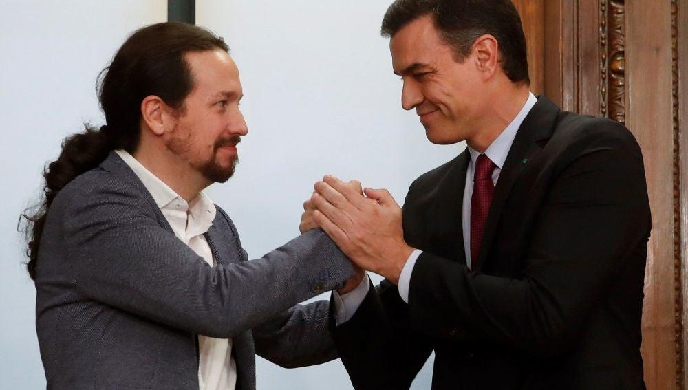 Pablo Iglesias y Pedro Sánchez se estrechan la mano sonrientes
