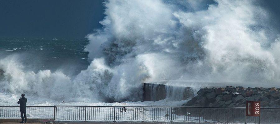 Un hombre mira las olas romper en una playa de Cataluña durante la borrasca Gloria