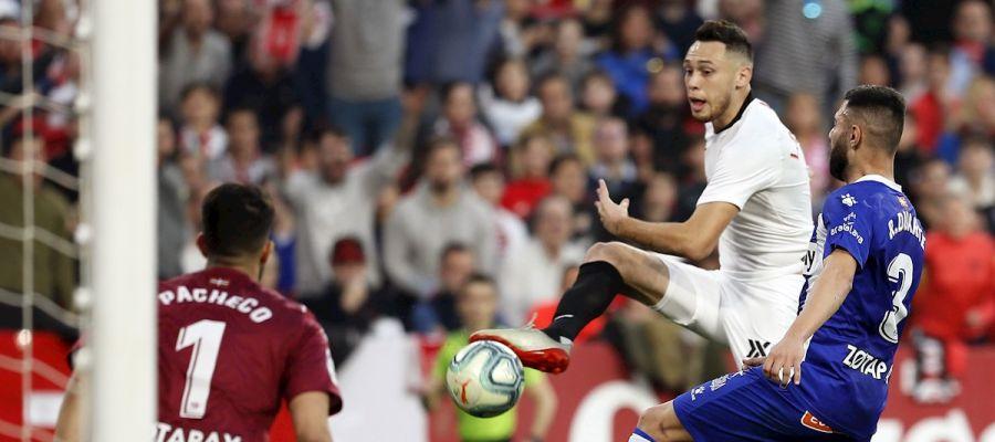El delantero argentino del Sevilla FC Lucas Ocampos (c) remata ante el defensa del Deportivo Alavés Rubén Duarte