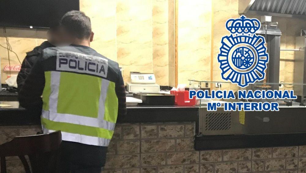 Un agente de la Policía Nacional en el establecimiento de Elda.
