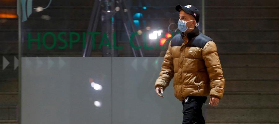 Un hombre porta una mascarilla sanitaria a su paso por la entrada principal del Hospital Clínic