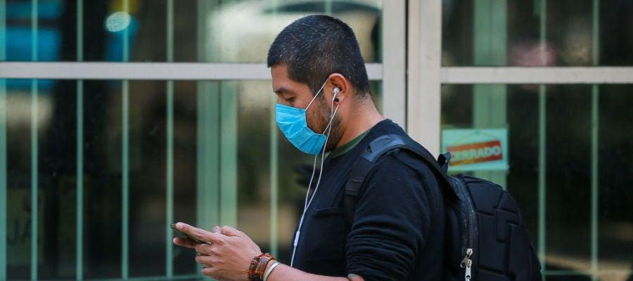 Coronavirus   Un hombre con mascarilla consulta su teléfono