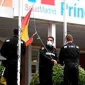 Miembros de Unidad Militar de Emergencias recogen la bandera de España en los exteriores del hospital Príncipe de Asturias de Madrid