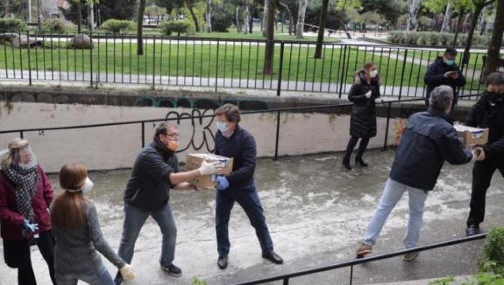 El alcalde de Madrid, José Luis Martínez-Almeida, ayuda a descargar unas cajas con alimentos