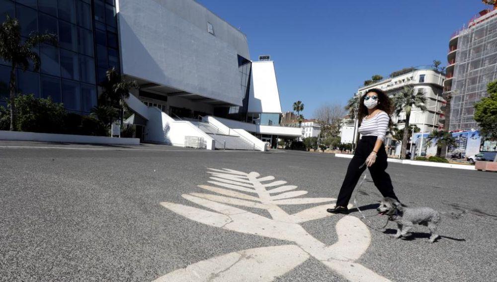 Una mujer con mascarilla pasea a su perro por la explanada que se extiende ante el Palais des Festivals de Cannes