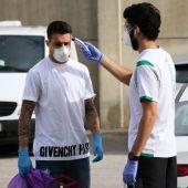 Un miembro del cuerpo médico del Betis toma la temperatura a Cristian Tello.