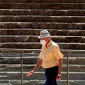 Una persona camina frente al Teatro Romano de Málaga protegiéndose con una mascarilla