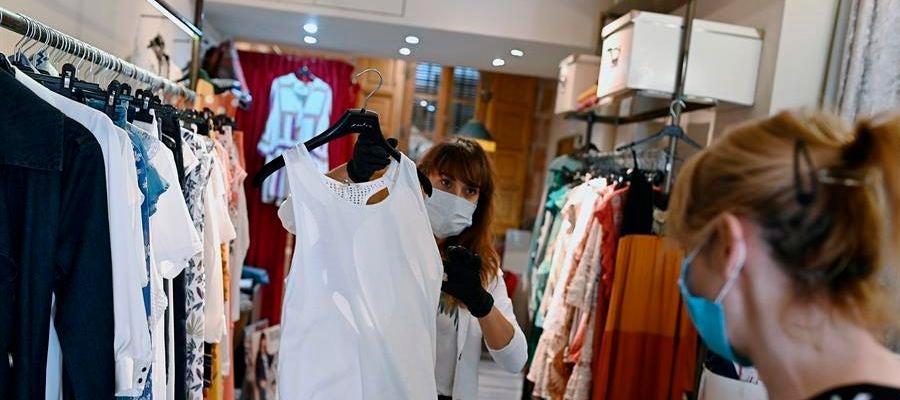 Una trabajadora muestra ropa a una clienta en un comercio de Alcalá de Henares, Madrid