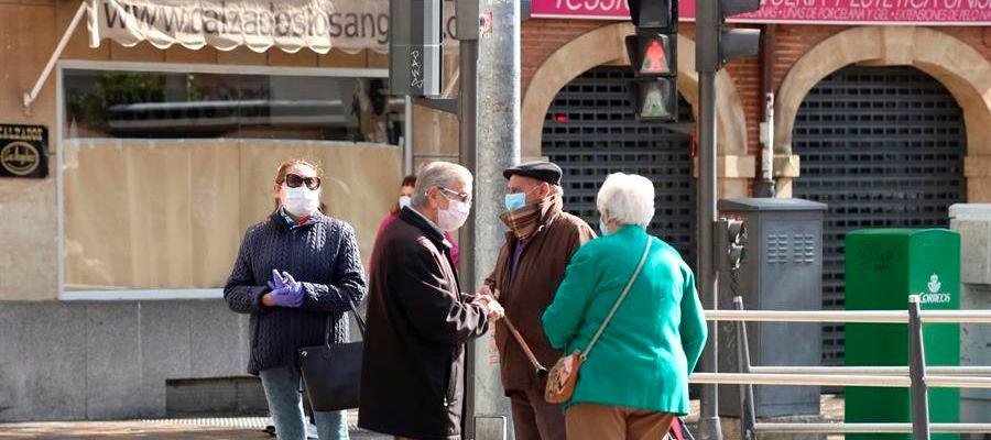 Personas mayores con mascarillas conversan en la calle