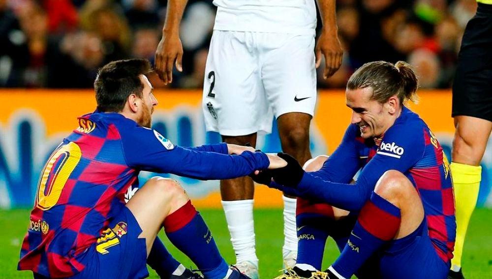 Messi y Griezmann se ayudan a levantarse del césped en un partido con el Barça.