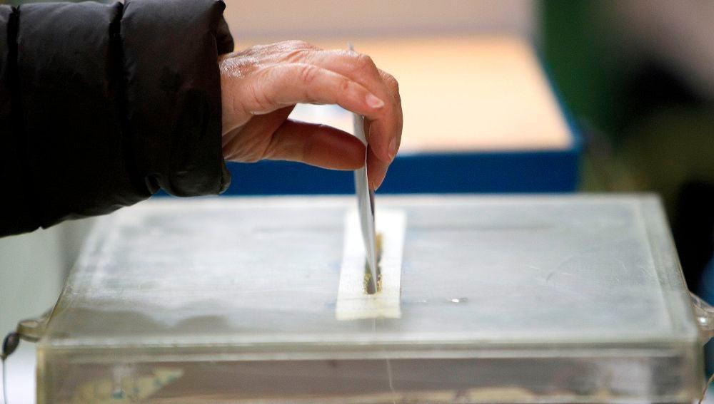 Una persona deposita su papeleta en una urna.