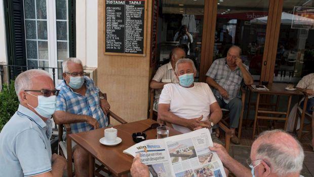 Un grupo de amigos tomando un café en un bar con la mascarilla puesta