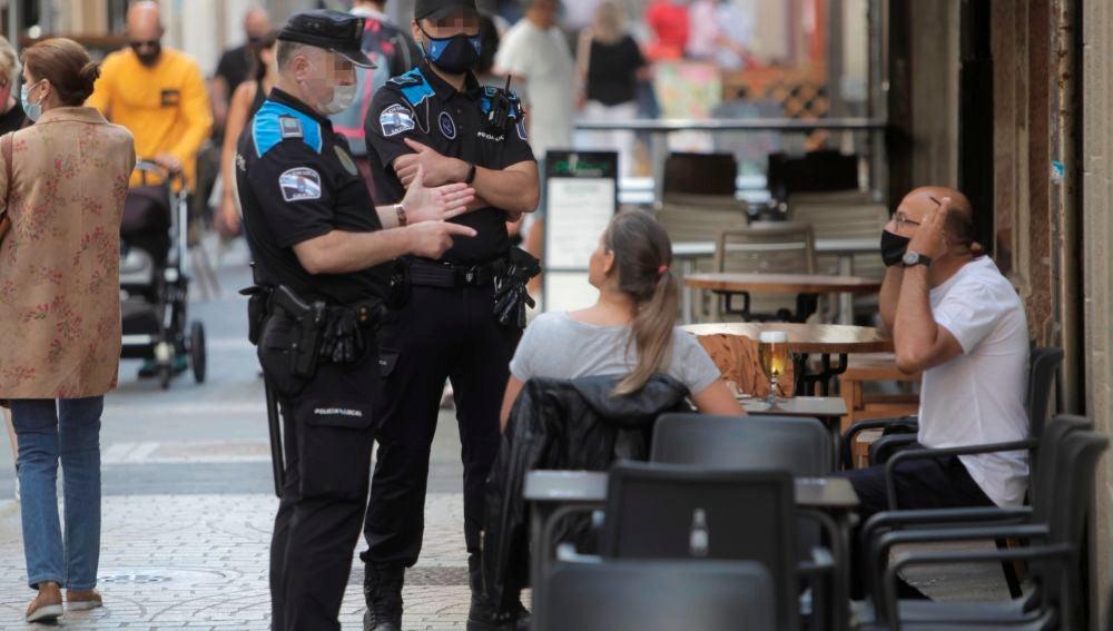 Dos agentes de la policía local de A Coruña se dirigen a un hombre que se encontraba fumando en una terraza de un bar