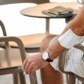 Un hombre fuma en la terraza de un bar con una mascarilla en el codo