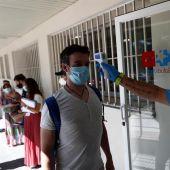 Un sanitario toma la temperatura a una de las personas que esperan su turno para realizarse una prueba de PCR dentro del Plan COVID-19 de la Comunidad de Madrid.