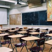 Imagen de archivo de un aula escolar con pupitres individuales.