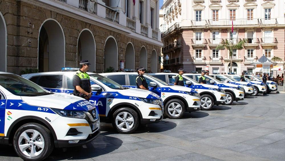 Policías locales junto a sus coches patrulla