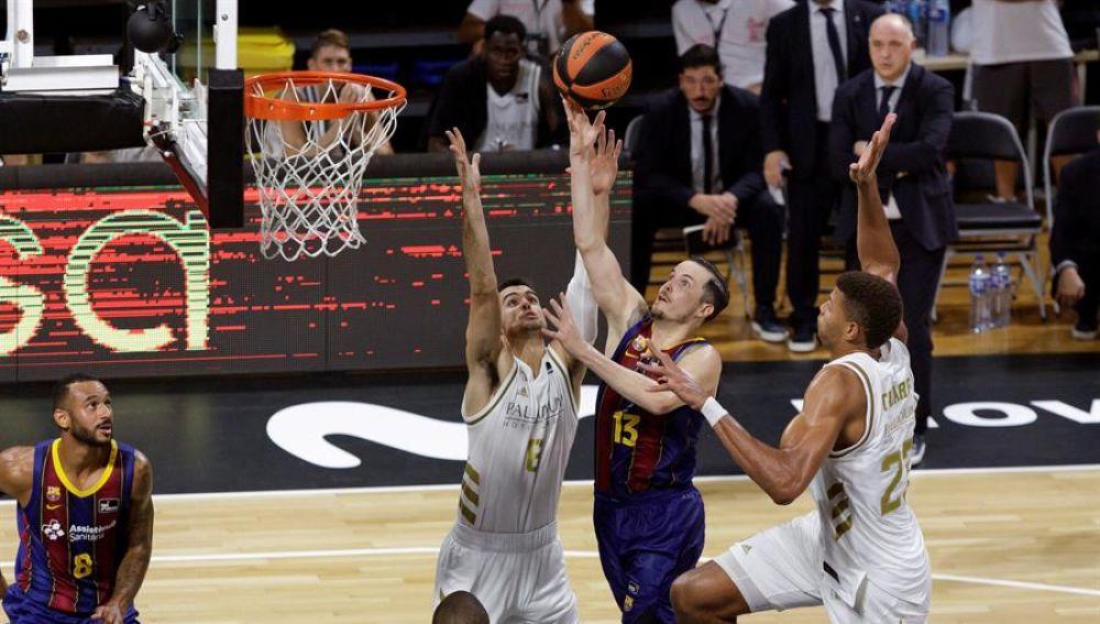 El base del Barça, Thomas Heurtel, lanza a canasta defendido por Alberto Abalde y Walter Tavares, del Real Madrid, durante la final de la Supercopa.