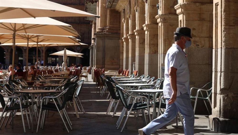 Un hombre con mascarilla pasa frente a una terraza de un restaurante de la plaza mayor de Salamanca.