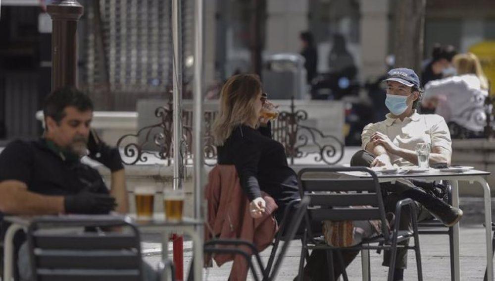 Clientes consumiendo en la terraza de un bar en horario diurno