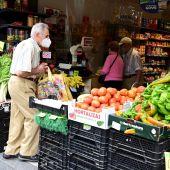 Vecinos con mascarilla compran en una frutería