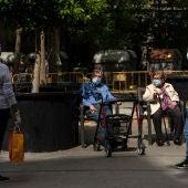 Varias personas mantienen una conversación con mascarillas en un parque en España.