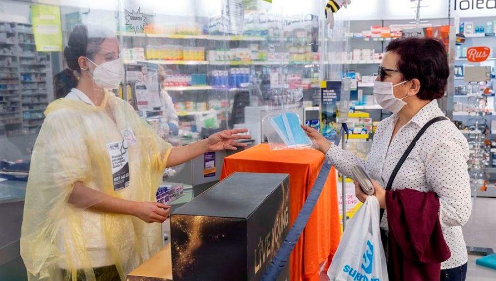 Una persona realiza la compra de varias mascarillas en una farmacia.