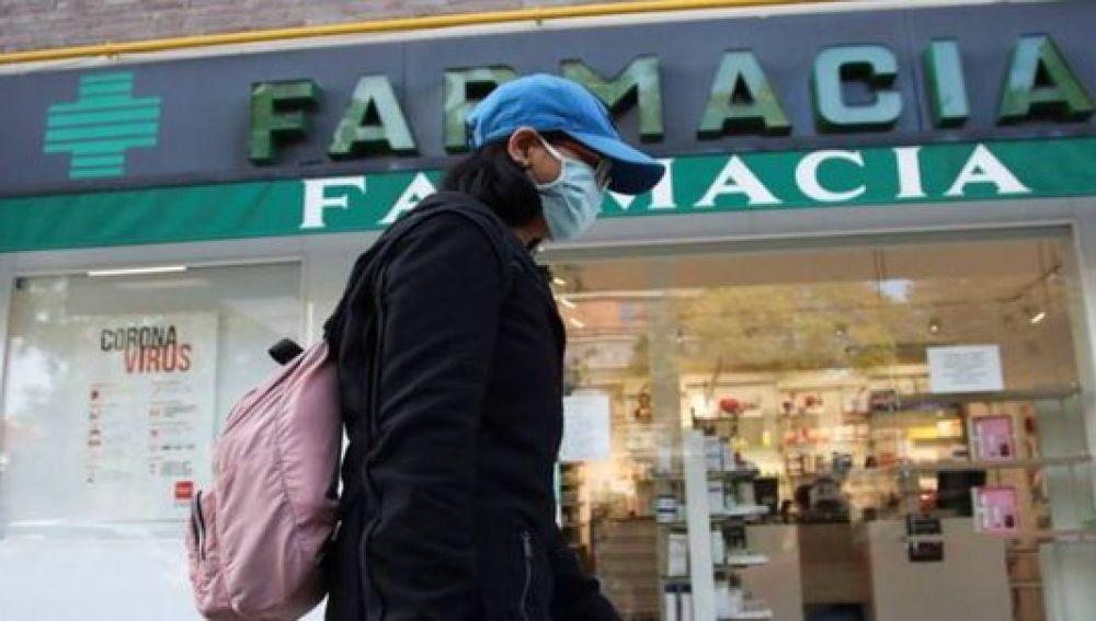 Una mujer pasa junto a una farmacia