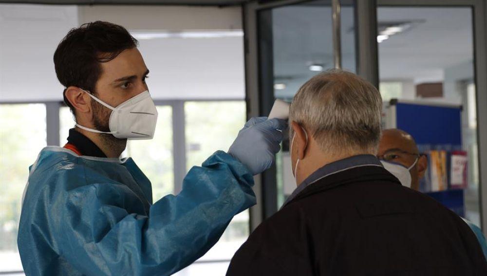 Personal sanitario del SERMAS toma la temperatura a una persona en la entrada del Centro de Mayores El Almendro (Madrid)