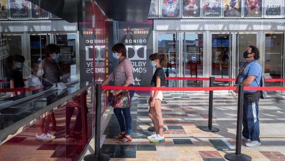 Varios espectadores hacen cola para comprar una entrada de cine