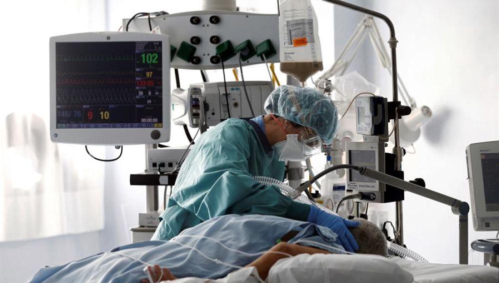 Una médico trata a un paciente de COVID-19 en una UCI.