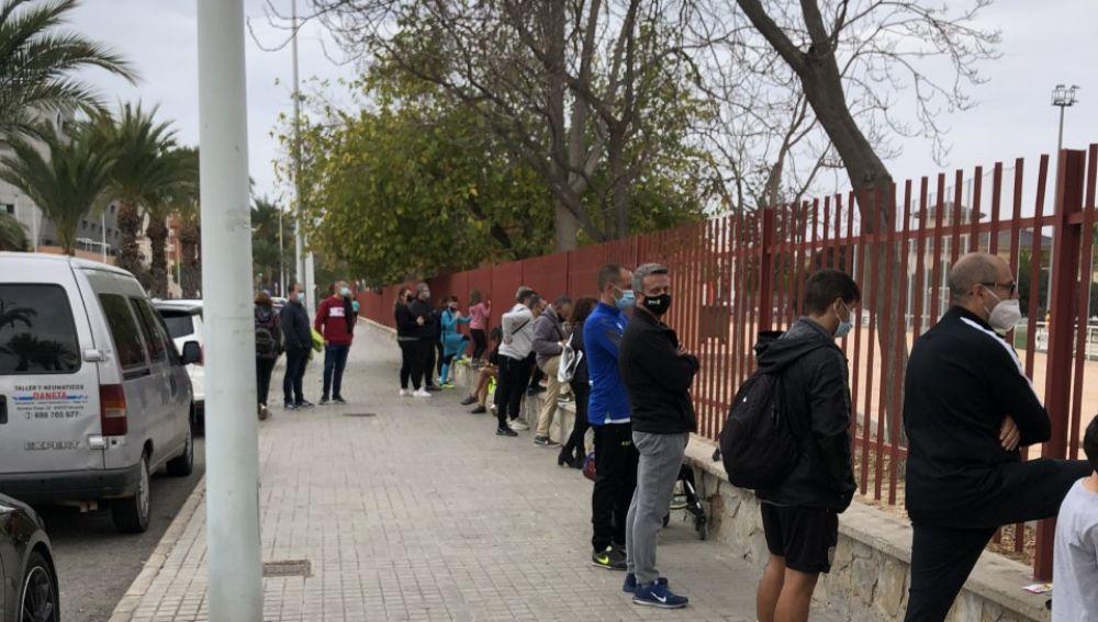 Personas junto al vallado de una instalación deportiva en Elche.