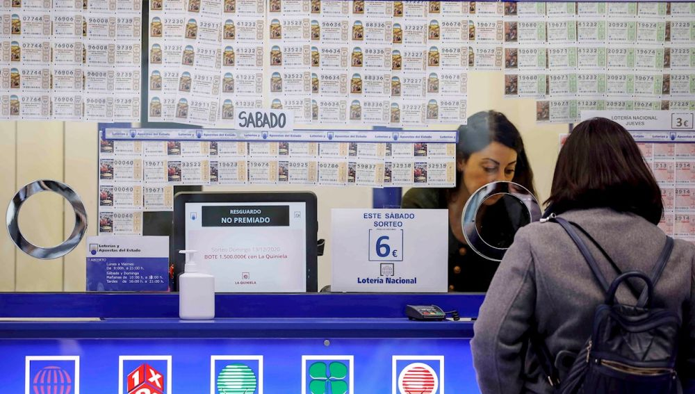 Una persona adquiere lotería en una administración