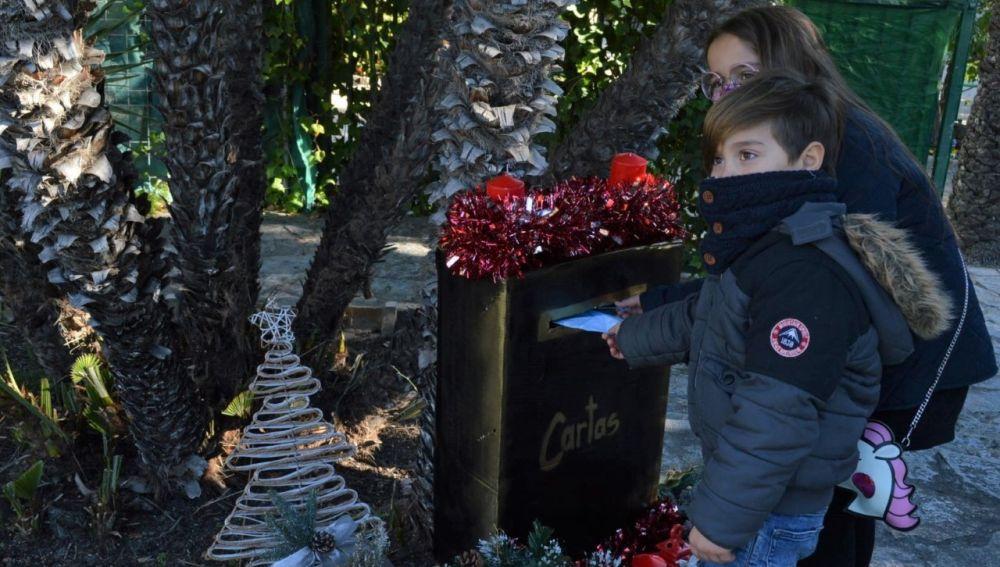 Niños depositan su carta a los Reyes Magos en el Buzón Real instalado en La Rotonda de Elche.