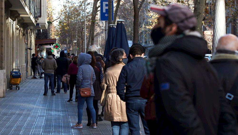 Multitud de personas hacen cola para hacerse una prueba PCR en Barcelona