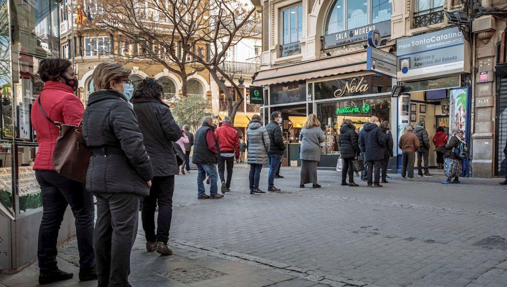 Varias personas hacen cola frente a una administración de lotería en Valencia