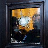 Dos policías observan a través del vidrio roto de una de las puertas del Capitolio de EEUU.