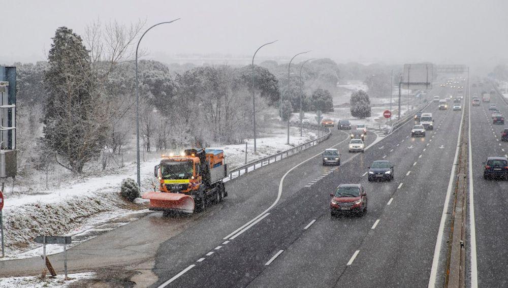 Un quitanieves trabaja mientras varios vehículos circulan por la A-5 a la entrada de Madrid durante el temporal de nieve