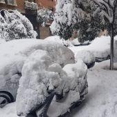 Coches y motos tapados por la nieve