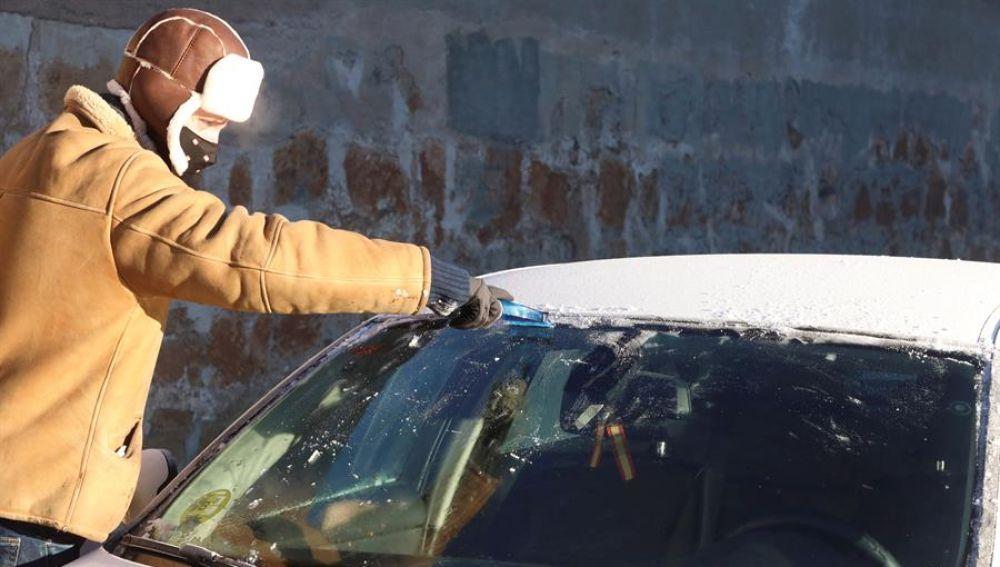 Un hombre quita la nieve de su coche