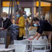 Un camarero limpia una terraza en Asturias