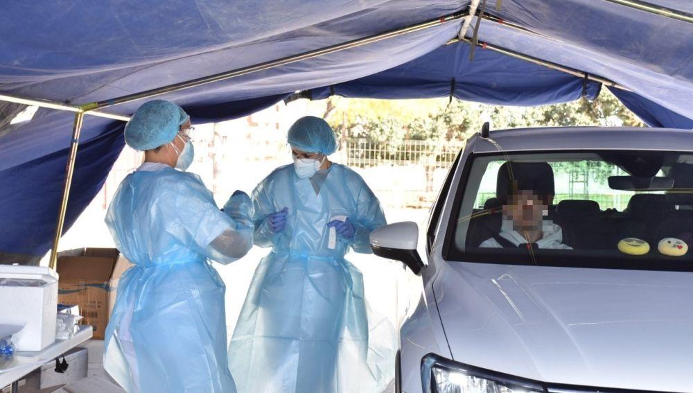 Un ciudadano espera en el interior del coche a ser sometido al test PCR de deteccion de coronavirus en Elche.