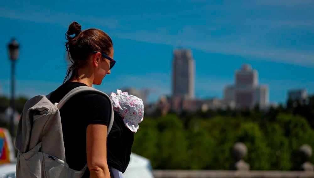 Una madre pasea con su bebé en Madrid.