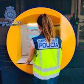 Una agente de la Policía Nacional de Elche en un cajero de la ciudad.