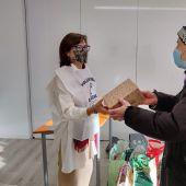 Una voluntaria de ASDEGAL entregando un paquete a un señor