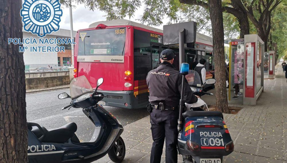 Un agente de la Policía Nacional frente a una parada de Tussam