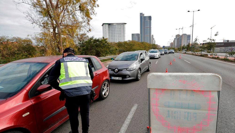 Un agente pregunta a una conductora el motivo de su desplazamiento en uno de los controles de Valencia.