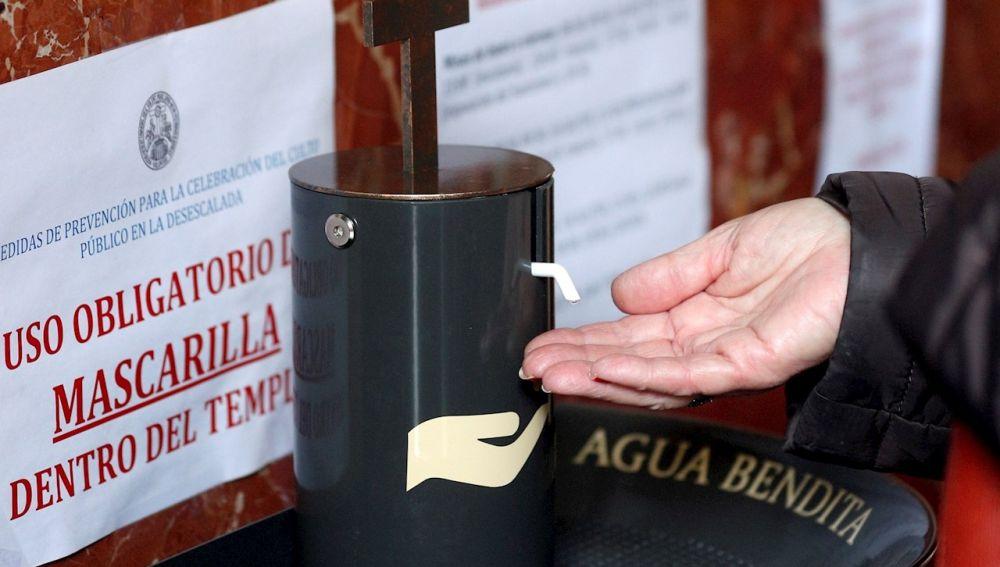 Una persona se pone agua bendita en una de los dispensadores automáticos de agua bendita