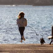 Un niña pasea a su perro