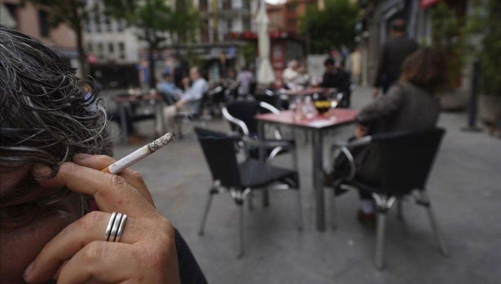 Imagen de archivo de una mujer fumando en una terraza.